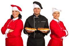 Equipo feliz de los cocineros con la pizza Fotos de archivo libres de regalías