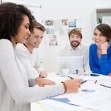 Equipo feliz del negocio que se sienta en una reunión Imagenes de archivo