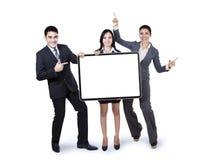 Equipo feliz del negocio que sostiene la cartelera Foto de archivo libre de regalías