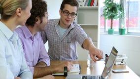 Equipo feliz del negocio usando el ordenador portátil y el planeamiento almacen de video