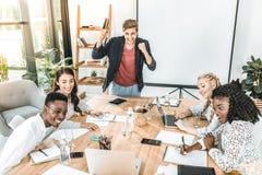 equipo feliz multicultural del negocio que tiene conferencia en el lugar de trabajo fotos de archivo