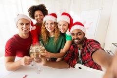Equipo feliz que celebra la Navidad en las fiestas en la oficina Foto de archivo libre de regalías