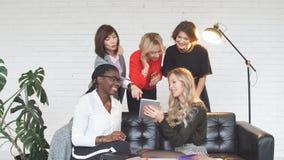 Equipo femenino del negocio joven multiétnico en el trabajo en oficina metrajes