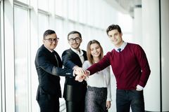 Equipo internacional del negocio que muestra la unidad con sus manos junto que se colocan en pasillo de la oficina fotografía de archivo