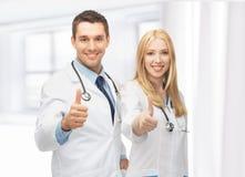 Equipo joven de dos doctores que muestran los pulgares para arriba Foto de archivo libre de regalías