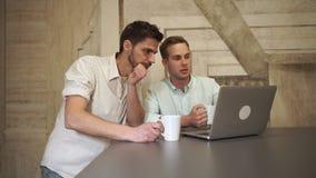 Equipo joven del negocio que mira en el ordenador y hablar almacen de metraje de vídeo