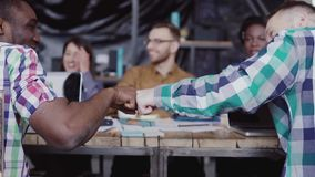 Equipo joven del negocio que trabaja junto cerca de la tabla, inspirándose Dos sirve el puño que se saluda almacen de video