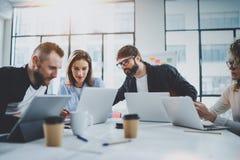 Equipo joven del negocio que trabaja junto en sala de reunión en la oficina soleada Compañeros de trabajo que se inspiran concept imagen de archivo