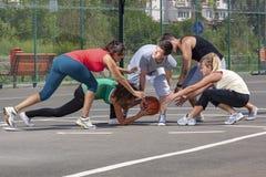 Equipo joven mezclado que juega a baloncesto en un patio imágenes de archivo libres de regalías