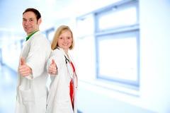 Equipo médico amistoso en capa del laboratorio con los pulgares para arriba Imagen de archivo libre de regalías