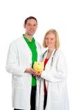 Equipo médico amistoso joven en capa del laboratorio con la hucha Imagen de archivo