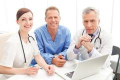 Equipo médico en el trabajo. Equipo médico alegre que se sienta junto en Imágenes de archivo libres de regalías