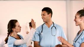 Equipo médico feliz que hace el alto cinco almacen de metraje de vídeo