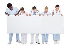 Equipo médico multiétnico que mira la cartelera en blanco Foto de archivo
