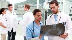 Equipo médico que mira la radiografía junto metrajes