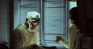 Equipo médico que realiza la operación en sala de operaciones del hospital metrajes