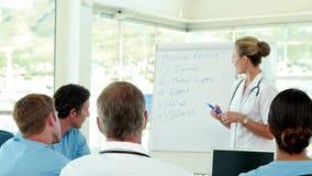 Equipo médico que tiene informe médico almacen de metraje de vídeo