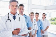 Equipo médico serio en fila foto de archivo
