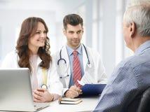 Equipo médico con el paciente mayor Foto de archivo libre de regalías