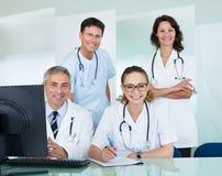 Equipo médico que presenta en una oficina Foto de archivo libre de regalías
