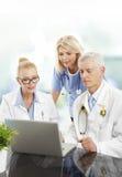 equipo médico que trabaja con el ordenador portátil Imagen de archivo libre de regalías