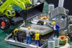 Equipo minúsculo de los juguetes de ingenieros que reparan compu del tablero de madre del circuito Imágenes de archivo libres de regalías