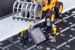 Equipo minúsculo de los juguetes de ingenieros que reparan el ordenador portátil del ordenador del teclado C Imagenes de archivo
