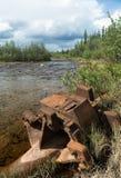 Equipo minero abandonado que aherrumbra a lo largo del st fluído del Alaskan Foto de archivo libre de regalías
