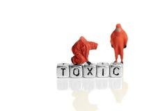 Equipo miniatura del modelo de escala en trajes químicos con la palabra peligrosa Imagen de archivo libre de regalías