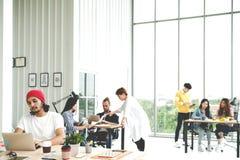 Equipo multiétnico acertado del negocio en la situación creativa de la forma de vida del trabajo rutinario, sentándose y hablando foto de archivo