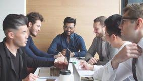 Equipo multiétnico creativo del negocio en la sala de conferencias moderna discutir resultados del trabajo almacen de metraje de vídeo