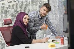Equipo multicultural internacional en el trabajo: mujer musulmán asiática y hombre caucásico foto de archivo