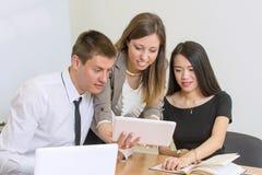 Equipo multicultural que mira una tableta fotografía de archivo