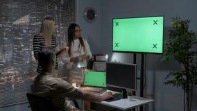 Equipo multirracial de diseñadores que hablan del modelo 3D del contenido personal en la pantalla y el monitor de computadora ver almacen de metraje de vídeo