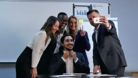 Equipo multirracial que toma el selfie en la reunión de negocios metrajes