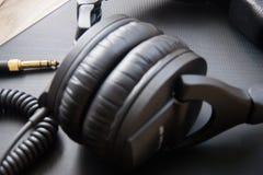 Equipo musical, auriculares profesionales del negro del estudio y cordón del enchufe Ciérrese para arriba desde arriba imagen de archivo libre de regalías