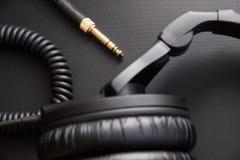 Equipo musical, auriculares profesionales del negro del estudio y cordón del enchufe Ciérrese para arriba desde arriba fotos de archivo