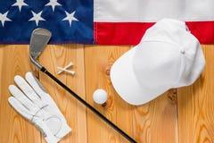 Equipo para el golf y una bandera americana en un piso de madera imagen de archivo