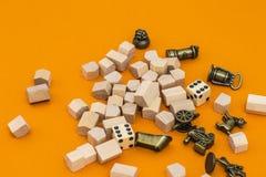 Equipo para el juego del monopolio en fondo anaranjado Fotografía de archivo