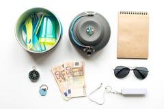 Equipo para el viaje con el compás y el efectivo en la opinión superior del fondo blanco Foto de archivo