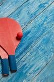 Equipo para jugar a tenis de la playa en el fondo de madera azul Foto de archivo