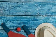 Equipo para jugar a tenis de la playa en el fondo de madera azul Imagenes de archivo