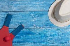 Equipo para jugar tenis y el sombrero de la playa en el fondo de madera azul Imagenes de archivo