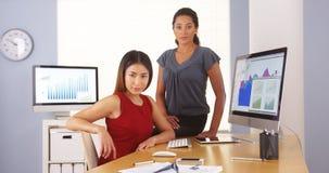 Equipo profesional de empresarias de la raza mixta que se sientan en oficina Imagen de archivo