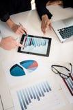 Equipo profesional que analiza la carta de barra exhibida en la tableta Fotos de archivo libres de regalías
