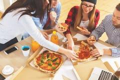 Equipo que come la pizza en el lugar de trabajo Fotos de archivo libres de regalías