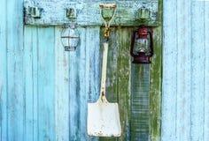 Equipo que cultiva un huerto, herramientas que cultivan un huerto con caída de la lámpara en la pared de madera Imágenes de archivo libres de regalías