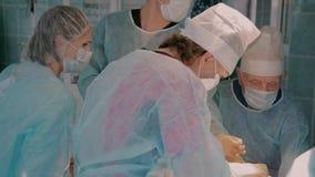 Equipo quirúrgico del hospital que termina una operación usando los instrumentos quirúrgicos metrajes