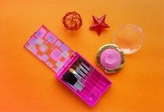 equipo rosado del maquillaje en fondo anaranjado brillante fotos de archivo