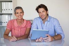 Equipo sonriente casual del negocio que trabaja en el escritorio usando la tableta Fotos de archivo